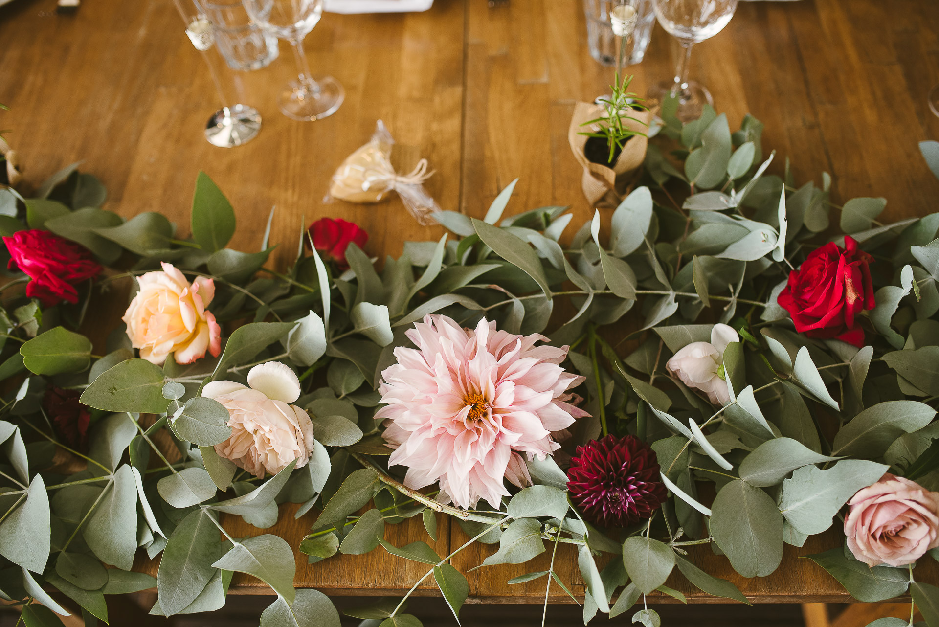 pastel flowers and eucalyptus leaves decorating a wedding table