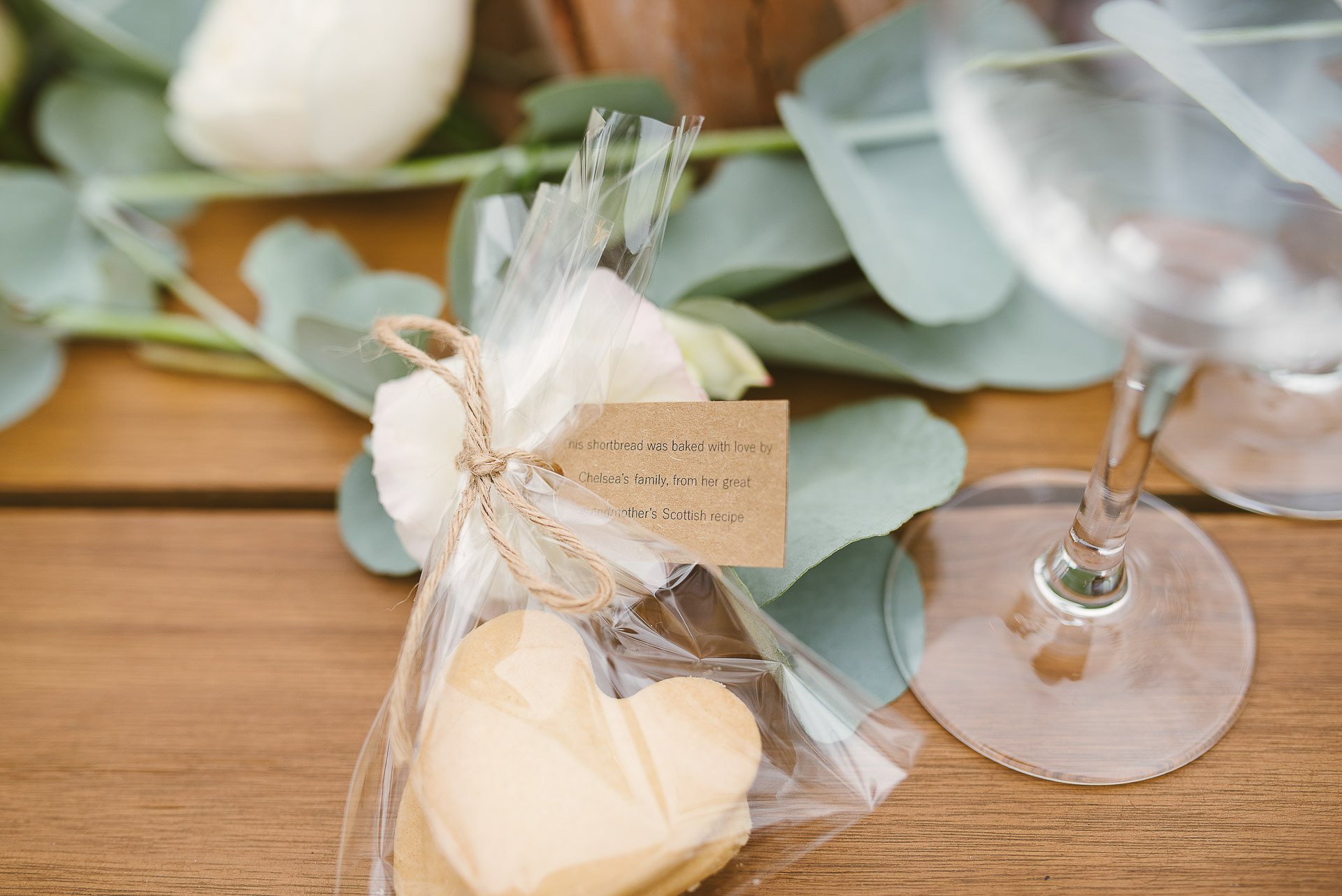 home made love-heart shaped shortbread gift wrapped for guests on a wooden wedding table