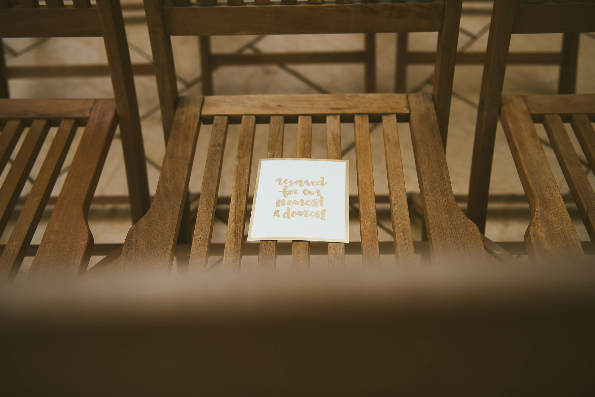reserved seat card placed on wooden seats at a beach road wines wedding