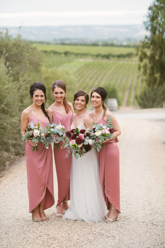 bride chelsea and three bridesmaids holding flowers by farmhouse flowers before wedding ceremony