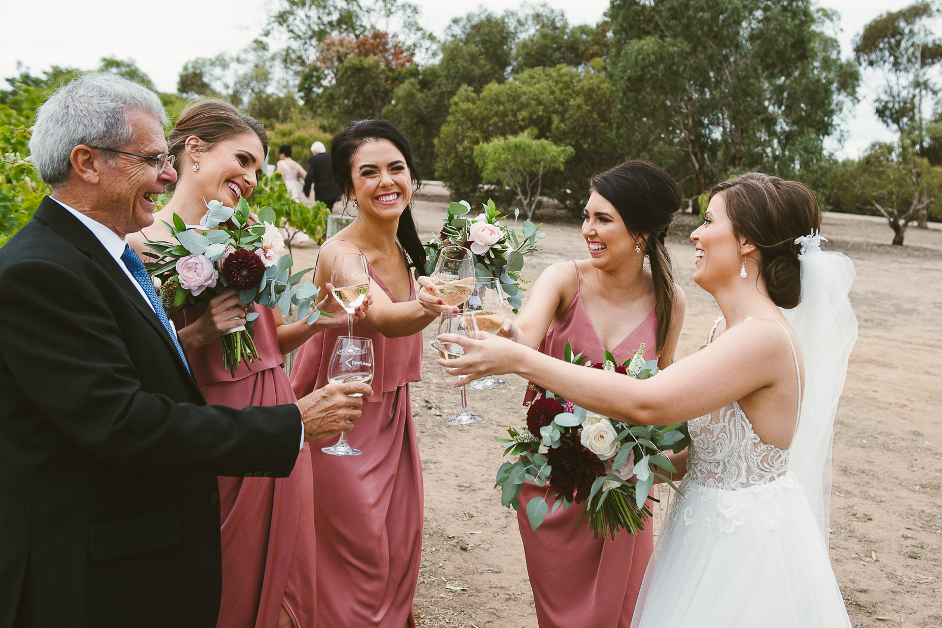 bridesmaids and bride and father enjoy a wine before the ceremony at beach road wines