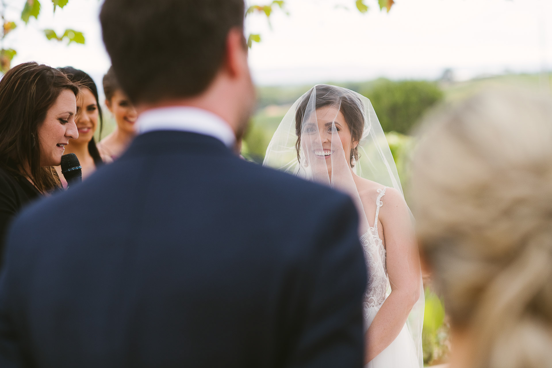bride smiling over grooms shoulder during wedding ceremony