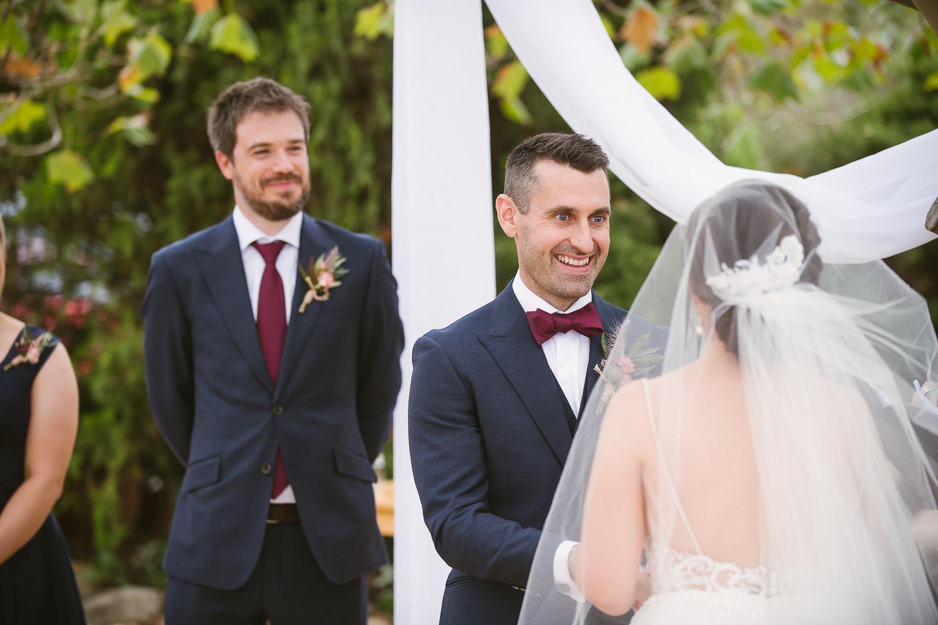 groom smiling over brides shoulder during ceremony at winery wedding