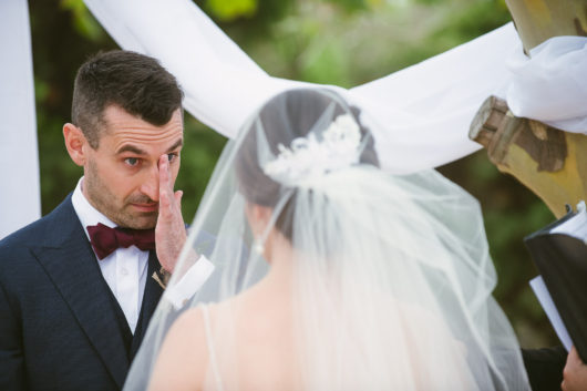 happy groom wiping a tear from his eye during winery wedding ceremony
