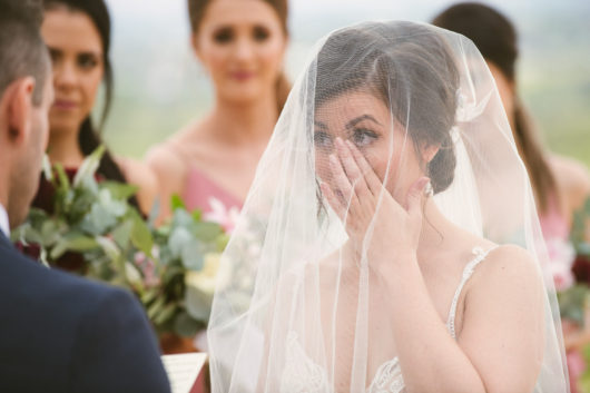bride wiping tear from her cheek during emotional wedding ceremony