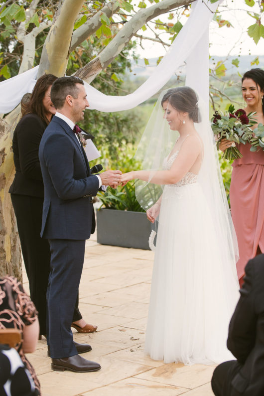 groom placing ring on brides finger in garden ceremony at beach road winery wedding